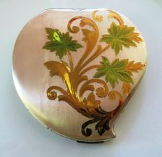 A vintage Elgin American woman's heart-shaped powder compact featuring a gold and green floral design on silvertone.