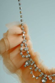 <3 this rhinestone strand necklace, featuring ruffle upon ruffle of pretty peach fabric.