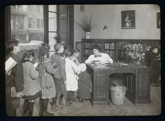 Children lined up at the Chatham Square Branch librarian's desk, 1910. [Photo via]