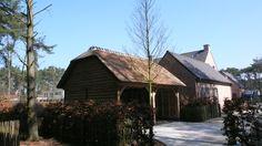 Eiken dubbele carport met rieten kap. Aan weerszijde is het dak afgewerkt met een wolfseinde.