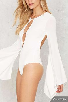 Three straps and you're fire.This bodysuit is white and features strappy detailing, cutouts at front and sleeves, control strap at back neck, low scoop back, bell sleeves. Pair it with a folk style skirt and chelsea boots.