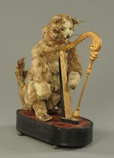 A 19th century musical automaton, in the form of a cat playing a harp, with clockwork movement and internal cylinder, raised on an oval ebonised base. Height 42 cm. #harp #automaton #Victorian