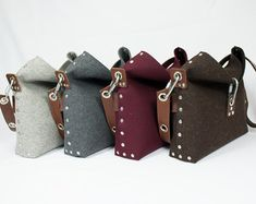 "Womans handbag which is handmade from 3 mm industrial wool felt, and is assembled using pop rivets. The strap is made from 100% vegetable tanned full-grain leather and backed with felt, which helps it slipping off your shoulder.  The front flap fastens with carabiner, and there are internal pockets for your phone and wallet.  Dimensions:  Length 10 / 25cm  Width 13 / 33cm  Depth 4"" / 10cm  This bag, like all my items, are designed and made by myself in London, UK. I do not hold a huge amount…"