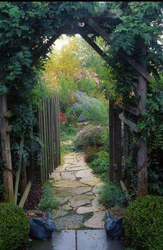 Lush garden through a wooden gate.