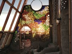 Earthship Biotecture - beautiful recycled glass wall with sunlight coming through