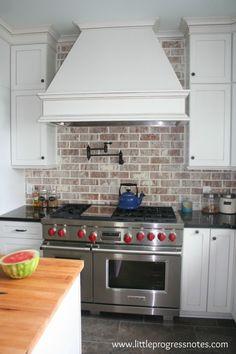 Brick backsplash white cabinets.  But that hood is too big I think.