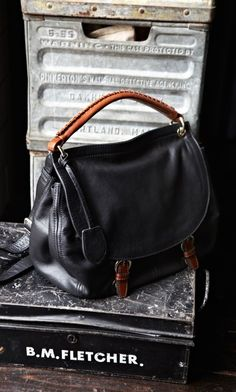 Soft black leather satchel bag with lovely brown leather handle. Comes with a black cross-body strap.