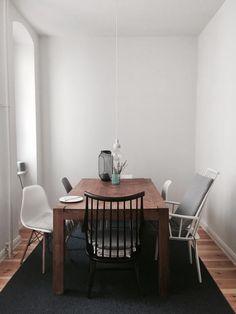 Essbereich mit rundem Tisch, grüner Wand und gelben Stühlen ...