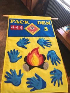 Cub Scout Wolf Den Flag - parent hands under boy hand. The boys wrote their initials on the felt and I outlined them with embroidery stitches. Mostly made from felt.