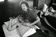 A nurse attempts to comfort a wounded U.S. Army soldier in a ward of the 8th army hospital at Nha Trang in South Vietnam on February 7, 1965. The soldier was one of more than 100 who were wounded during Viet Cong attacks on two U.S. military compounds at Pleiku, 240 miles north of Saigon. Seven Americans were killed in the attacks