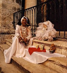 Woman in Santeria clothes on church step