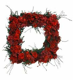 """Red Rose Wreath by Wind & Weather. $229.00. Red Rose Wreath. This brilliant red rose wreath is crafted in Arkansas from preserved red roses and red brick hydrangea. The luscious red tones and unique square shape makes the perfect statement for your home. Size 18""""H x 18""""W Dia. Shipping Allow 2-3 weeks for delivery."""
