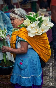 This Happened to Me The First Time in My Travels - Los Angeles Travel Photographer — Jean Huang Photography - Senior-Lady-in-Traditional-Costume-Buying-Cala-Lilies-in-Sunday-Market-of-Cuetzalan-Mexico-Copyrigh - Los Angeles Travel, Mexico Culture, Mexican Dresses, Mexican Folk Art, Travel Photographer, Hippie Style, Boho Hippie, Photos Du, People Around The World