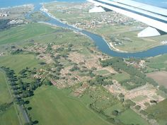 the vast archaeological site of Rome's ancient port city Ostia Antica seen from the air