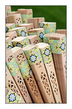 Keep Your Guests Cool - Sandalwood fans with ends wrapped with paper to coincide with wedding color decor