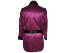 This is a vintage smoking jacket or short dressing gown/robe featuring a striking magenta colour with black abstract paisley type printed motif. The piece has a shawl collar in black satin and a matching sash belt. It has a breast pocket and applied pocket at either side, and the trim