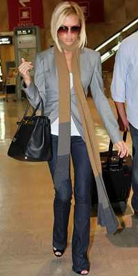 Victoria Beckham in jeans and grey blazer.