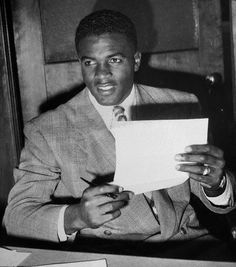 Jackie Robinson holding his contract to play with the Brooklyn Dodgers in 1947.