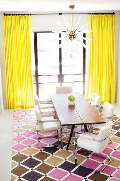 Welcoming contemporary dining room boasts glass patio doors covered in canary yellow curtains hung facing a mid-century modern dining table seating modern white leather dining chairs on a colorful lattice rug illuminated by an Arteriors Hanley Chandelier. Pink Dining Rooms, Yellow Dining Room, Patio Door Curtains, Dining Room Curtains, Modern Patio Doors, Modern White Living Room, Vintage Dining Chairs, Dining Table, Yellow Curtains
