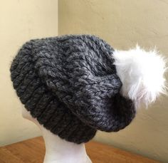 Cold weather calls for warm, mood-boosting accessories like the Miabeanie winter hat with a furry white pom pom.    This handmade beanie is one of a kind and is sure to turn heads. It will keep you warm during cool days and chilly nights while adding a splash of style to any outfit.     The entire hat is crafted using thick yarn which adds to the overall texture of the hat. It is chunky, but still soft and comfortable to wear. The adorable furry pom pom adds an extra element of fun and will…
