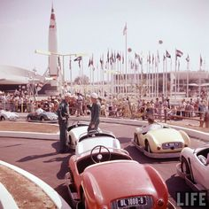 Disneyland opening day 1955 - Autopia with TWA Rocket to the Moon and Flag of Nations in background. From Life Magazine, photos by Allan Grant and Loomis Dean. Color corrected by United Style Disneyland Opening Day, Disneyland Secrets, Disneyland Tomorrowland, Disneyland Paris, Disneyland History, Disneyland California, Vintage Disney Posters, Vintage Disneyland, Old Disney