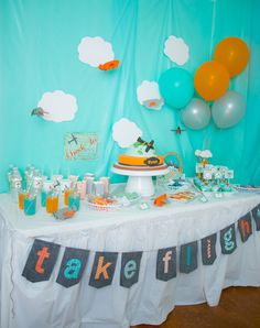 I set the scene with a fun sky backdrop by cutting clouds from foam board and covering them in white felt. I covered the wall with a sky blue plastic tablecloth then hung paper airplanes! Evan loved it. There were also sweets treats galore that coordinated with our theme as well as a cute felt banner. Evite Airplane Party by Ella & Annie