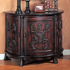 Refined and elegant in design, this Bombe Chest is sure to the catch the eye of anyone who enters your home. The chest features bold arabesque carvings that accentuate the rich cherry finish giving it a classic appearance. Lining the top is beautiful black marble in a demilune, half-moon shape. Behind all the intricate detailing of the chest are three doors that open up to provide extra storage. With a spacious top you will definitely showcase your accessories and home decor with elegance.