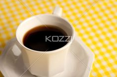coffee cup without spoon - Coffee cup on a yellow tablecloth without a spoon.