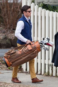 Looking good: Donning a pair of shades and holding onto a bag of golf clubs, The Paperboy star completed his character's look with sleek hair