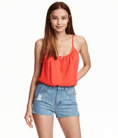 Flared camisole top in woven viscose fabric with narrow, adjustable shoulder straps and a button placket.