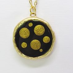 A personal favorite from my Etsy shop https://www.etsy.com/listing/505783403/modern-gold-and-black-circle-pendant