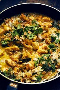 Indian chicken.4 beaux blancs de poulet - 1 petite botte d'oignons nouveaux - 20g de beurre - 1càs de curry en poudre - 1càc de graines de coriandre - 1càc de graines de fenouil (vous pouvez aussi utiliser du cumin ou du carvi) - 1 petite poignée de feuilles de curry (facultatif) - 1 boîte de lait de coco - 2càs d'amandes effilées légèrement grillées - 1 petit bouquet de coriandre - sel