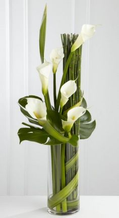 Eternal friendship vase arrangement - a stylized vase arrangement of white calla lilies and assorted foliages.