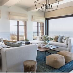 A beach living room in navy, blues and tan, with upholstered furniture, leather ottomans, tan Roman shades and printed pillows. Beach Living Room, Coastal Living Rooms, Home Living Room, Living Spaces, Coastal Living Magazine, Beach Cottage Decor, Coastal Decor, Coastal Style, Seaside Home Decor