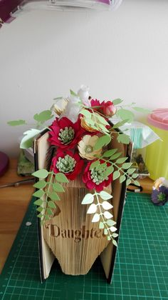 Made by Carol Jenkins - I am into book folding I find it very therapeutic as I get lost in time. This one I have made is to take to my daughter in Turkey where she is working. The books I buy are mainly from charity shops or donations that are gratefully received. The flowers and greenery are from the Florartistry range which i am trying to perfect at the moment. I cover the books with whatever is appropriate for the book or the person it is for. Fabric Flowers, Paper Flowers, Diy Paper, Paper Crafts, Charity Shop, Book Folding, Create And Craft, Love Craft, Fundraising