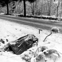 Deceased American soldier along a road in the Ardennes.