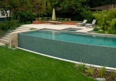 Pool wall is fence. Gate at base of steps. Plants surrounding pool protecting it. Built-in seating Pool wall is fence. Gate at base of steps. Plants surrounding pool protecting it. Built-in seating Sloped Backyard, Small Backyard Pools, Backyard Pool Designs, Small Pools, Swimming Pools Backyard, Swimming Pool Designs, Pool Landscaping, Backyard Patio, Infinity Pool Backyard