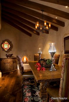 In the dining room, a hand-carved chest made in the Visions workshop sits beneath a stained-glass quatrefoil window. The rug is a Moldavian Bessarabian from the 1920s, an excellent example of the classic Victorian rugs made during that era. Traditional Southwestern elements, like the kiva fireplace and the vigas, are a graceful addition.