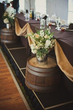 Barrels with tin vases for flowers. I like how they cut them in half