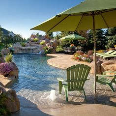 Lagoon swimming pool with vanishing edge, rock waterfall, beach entry with rock accents, water geysers, and travertine patio...incorporate slide into waterfall