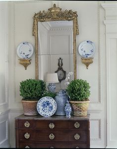 It's Friday and it's Fabulous in Blue and White... boxwood in indoor pots, blue and white china plates, fabulous mirror with urn