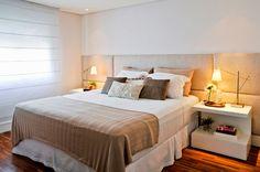 Quarto com cabeceira estofada de tecido bege, sendo mais larga no meio, onde fica a cama + criados de laca branc