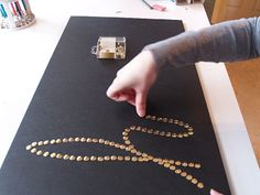 Lightweight, inexpensive Push Pin Art - frame foamboard and use shiny brass thumbtacks to spell out whatever you would like to say