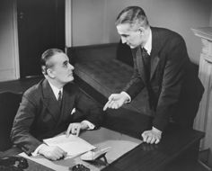 Two Businessmen Talking At Desk Stock Photo 82174335
