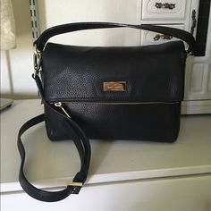 """Black leather Kate Spade purse Hip never used (new with tags - $328) black leather kate spade purse with a short strap and adjustable shoulder strap. About 10.5"""" long, 8ish inches tall, and ~4"""" wide at the base (it tapers towards the top).  I stored it under my bed and it got a little squished but those little marks (3rd pic)  might come out. Inside is lined with pink kate spade embossed fabric and has one zip pocket and two open pockets. The flap of the bag also unzips to reveal a lined…"""