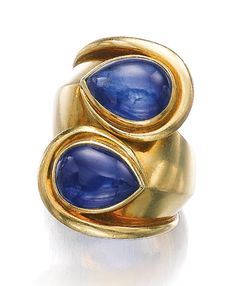 SAPPHIRE RING, SUZANNE BELPERRON, 1973.  Of toi et moi design, set with two pear-shaped cabochon sapphires, to an architectonic gold mount, size 52, French assay and maker's mark for Darde & Cie.