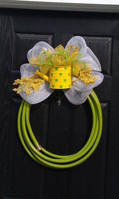 Waterhose wreath. I cut the watering can in half to make it lay flatter against the bow.  The bow is made of different widths of plastic ribbon.  Everything is secured with florist wire. I only used about half of a hose.