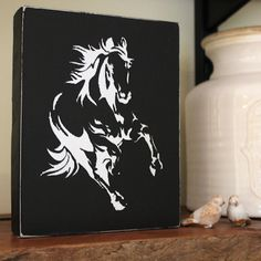 Black painted wooden block with the image of a white running horse. Running Horses, Horse Stalls, Wooden Blocks, Image, Wood Blocks, Stables