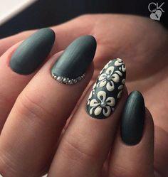 Nail art design on almond shaped nails. Colours: matte dark emerald green, white