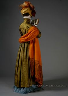 """""""Isabelle"""", from the exhibition """"Napoleon and the Empire of Fashion"""". Lancaster-Barreto collection. Pelisse: Moss green silk taffetas pelisse with sky blue silk lining and Point de Bruxelles lace collar, French or English, ca. 1811. Pumpkin-colored cashmere shawl, Indian, ca. 1810. Gold brooch with sea shell cameo and paste jewels, English/Italian, 1812-1815. This is the back view"""